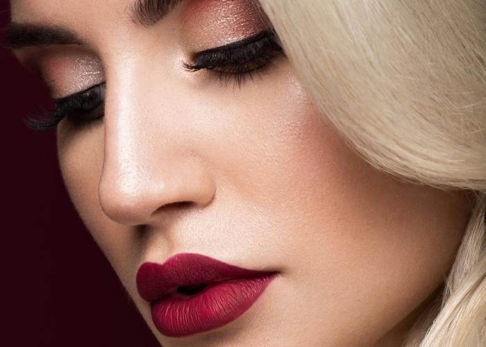 maquillage pour yeux vert, blonde aux lèvres rouge matte et fards à paupières brillantes de nuance rose