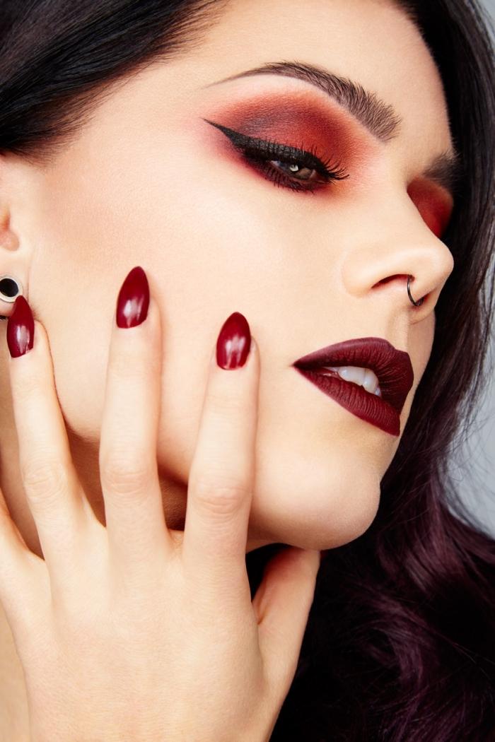maquillage foncé aux lèvres bordeaux mat et yeux maquillés en fards à paupières rouge et eye-liner noir