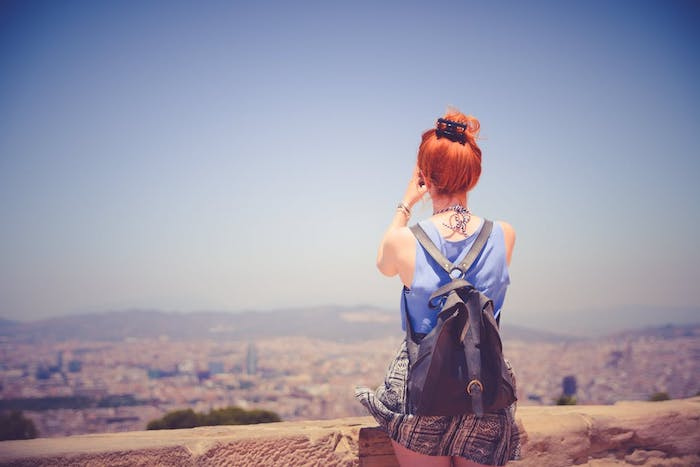 tie and dyre roux, nuance de rouge, cheveux attachés sur le dessus de la tete, chemise bleue, sac à dos tendance