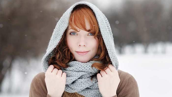 exemple de cheveux roux cuivré coupe au carré ondulé avec frange sur le front, écharpe gris et pull marron