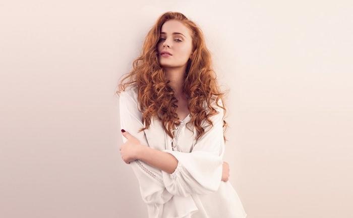 idée de couleur blond cuivré femme aux cheveux longs bouclés, sophioe turner, chemise blanche