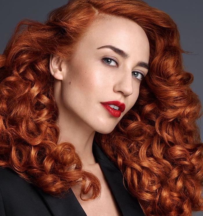 exempel de coloration roux foncé, cheveux volumineux avec des grosses boucles et tailleur femme noire