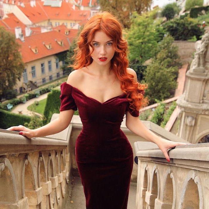 couleur de cheveux roux foncé, une coiffure élégante de type princesse, cheveux longs ondulés et robe rouge bordeaux