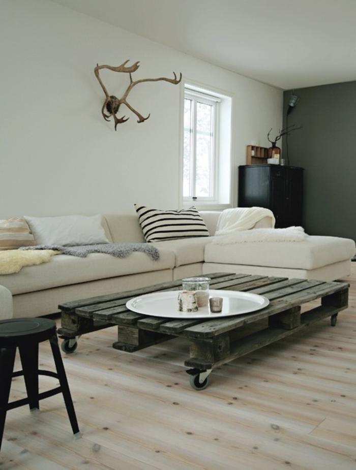 une table basse en palette qui s'accorde parfaitement avec la déco en couleurs neutres et textile qui mise sur les textiles