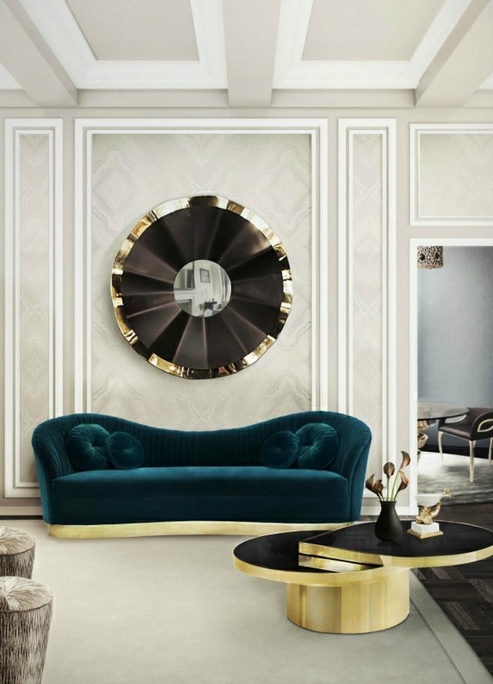 salon de luxe avec canapé en velours en bleu pétrole, grand miroir rond sorcière, table ronde avec deux niveaux avec base dorée et des plans en noir, revetement du sol en marbre blanc, des frises rectangulaires aux murs en gris et blanc, plafond en blanc et gris, divisé en grands rectangles