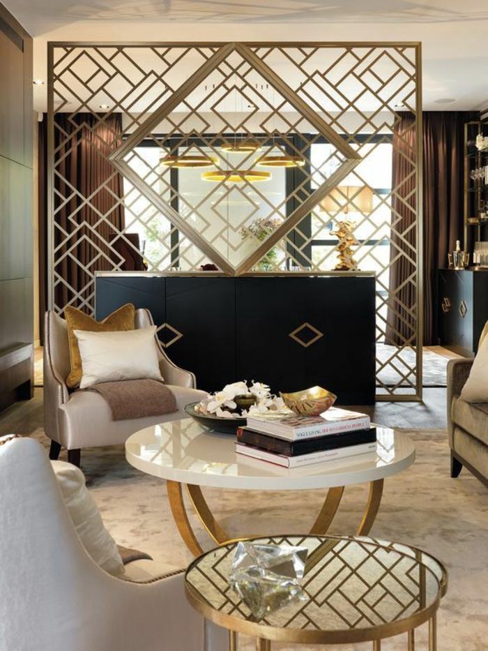 deco salon dans une maison moderne de luxe, avec une multitude d'éléments en couleur dorée, table ronde avec plan blanc et pieds en métal doré, fauteuils en tissu irisé couleur lavande
