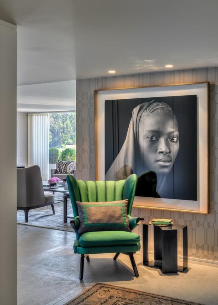amenagement salon avec grande photographie en noir et blanc au cadre doré, fauteuil en vert avec coussin en vert et marron, table en métal forgé en gris fumé, tapis oriental