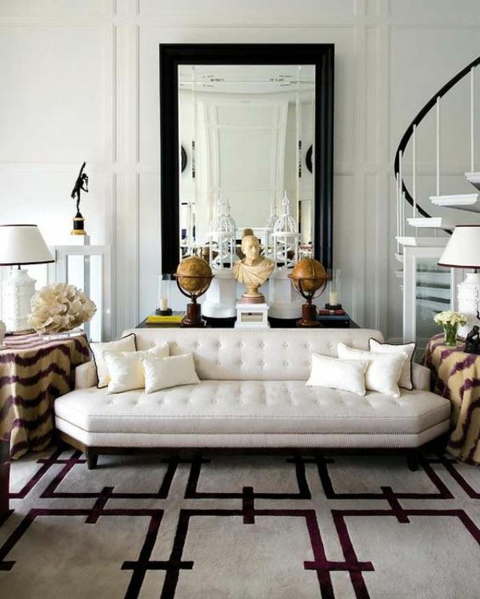 deco sejour avec tapis au sol en couleur bordeaux et gris, miroir rectangulaire au mur au cadre en noir, canapé en blanc, entouré de deux tables avec des nappes en tissu en rayures beige et marron