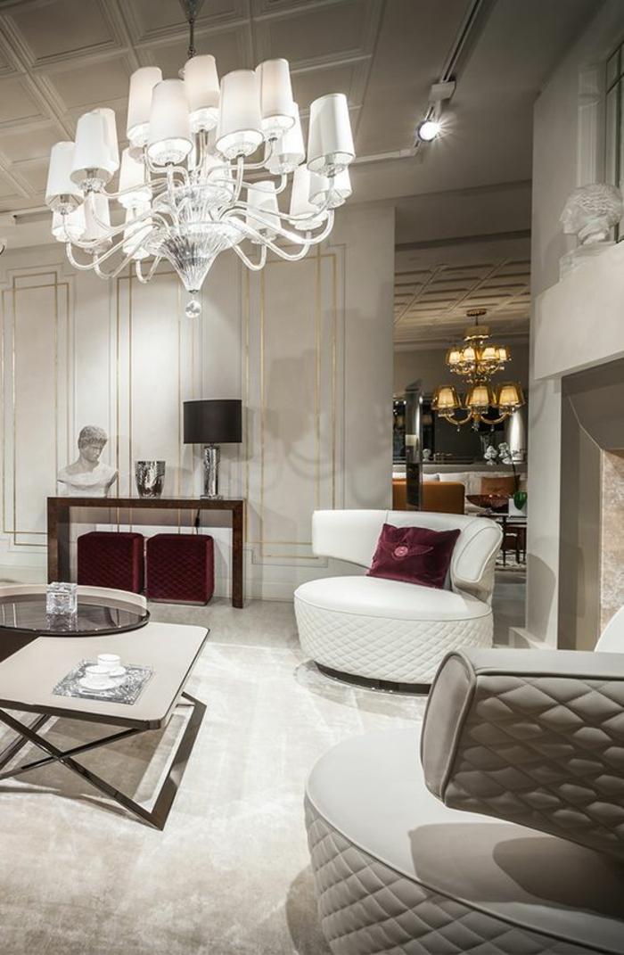 amenagement salon très luxueux, grand luminaire baroque aux multiples mini luminaires avec des abat-jours blancs, table carrée et ronde, grande cheminée en gris et blanc, fauteuils semi-ronds en gris pastel et blanc design futuristique