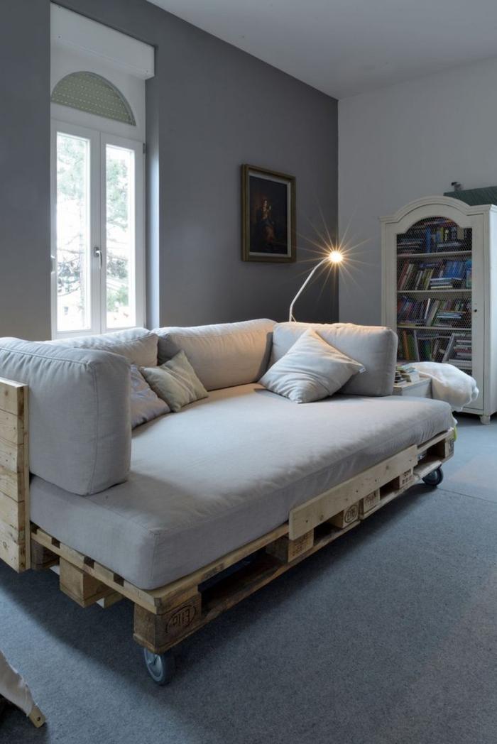 salon gris avec un canapé en palette sur roulettes équipé d un matelas et des coussins assortis