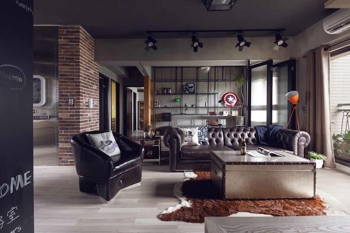 meubles style industrielle dans un salon industriel vintage, canapé en cuir marron, table basse coffre, parquet marron, fauteuil noir, mur en briques, etagere industrielle metal sur le fond, projeceurs