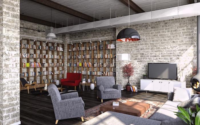 deco style industriel avec canapé et fauteuils gris, table absse en bois sur roulettes, bibliotheque bois, suspension gris anthracite, mur en briques