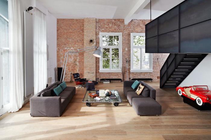 table basse industrielle en verre à roulettes, canapé gris, parquet clair, mur en briques, mezzanine, luminaire indus
