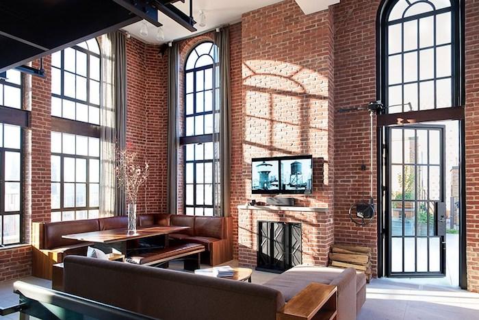 déco loft industriel, murs et cheminée en briques, canapé marron, table et banc en bois, sol en dalles à effet béton