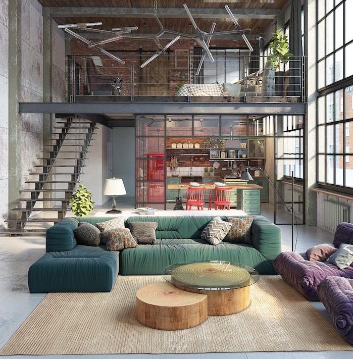 exemple de salon industriel moderne avec canapé vert et bleu, tables basses en tronc de bois, tapis beige, fauteuils mauves, cuisine séparée avec verrière