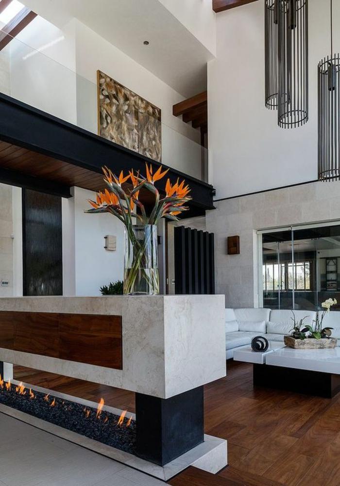 salon de luxe, deco salon, cheminée moderne en marbre blanc et noir, canapé blanc et table carrée blanche, tableau aux motifs ethno, parquet en couleur marron et cerise
