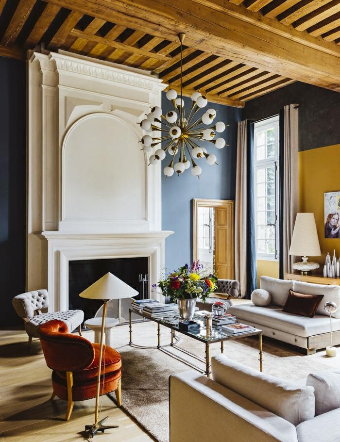 deco salon design, idée deco salon avec des poutres en bois clair au plafond, luminaire en forme de boules en verre blanc opaque, fauteuil en orange, canapés en couleur crème