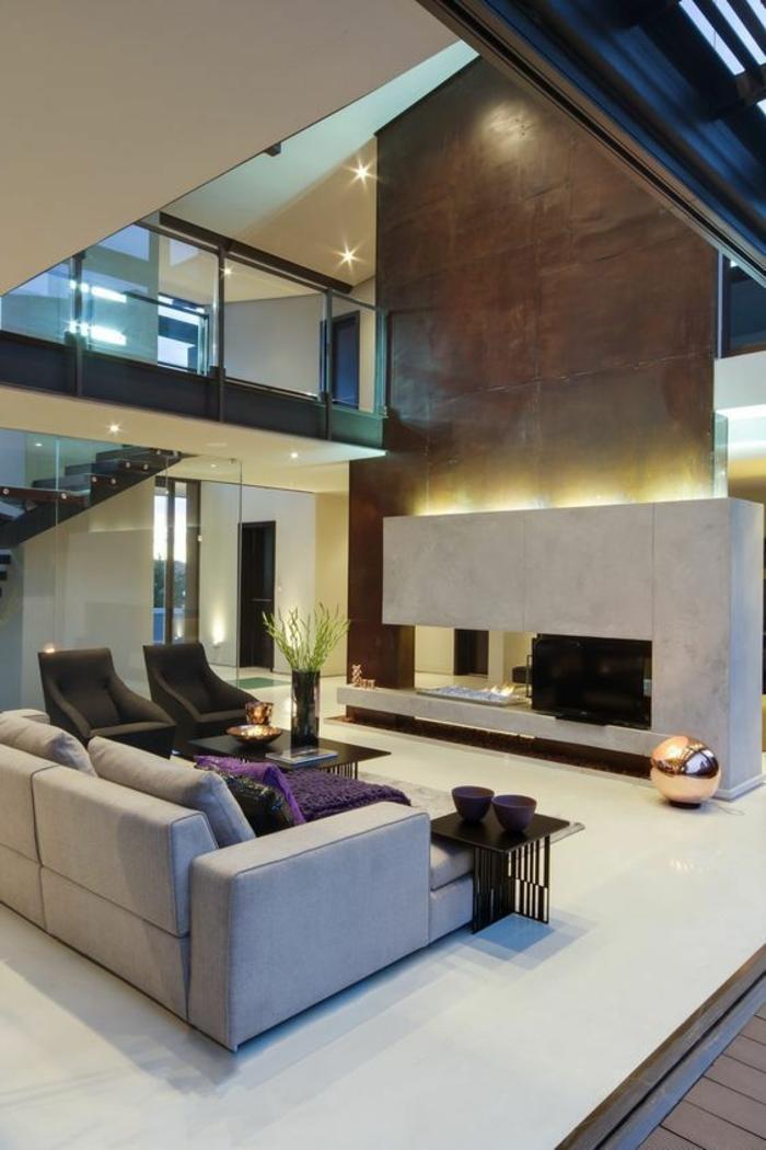 maison moderne de luxe, espace très grand, grande cheminée en pierre blanche avec un tube énorme revêtu de bronze pour la sortie des fumées, canapé en gris clair