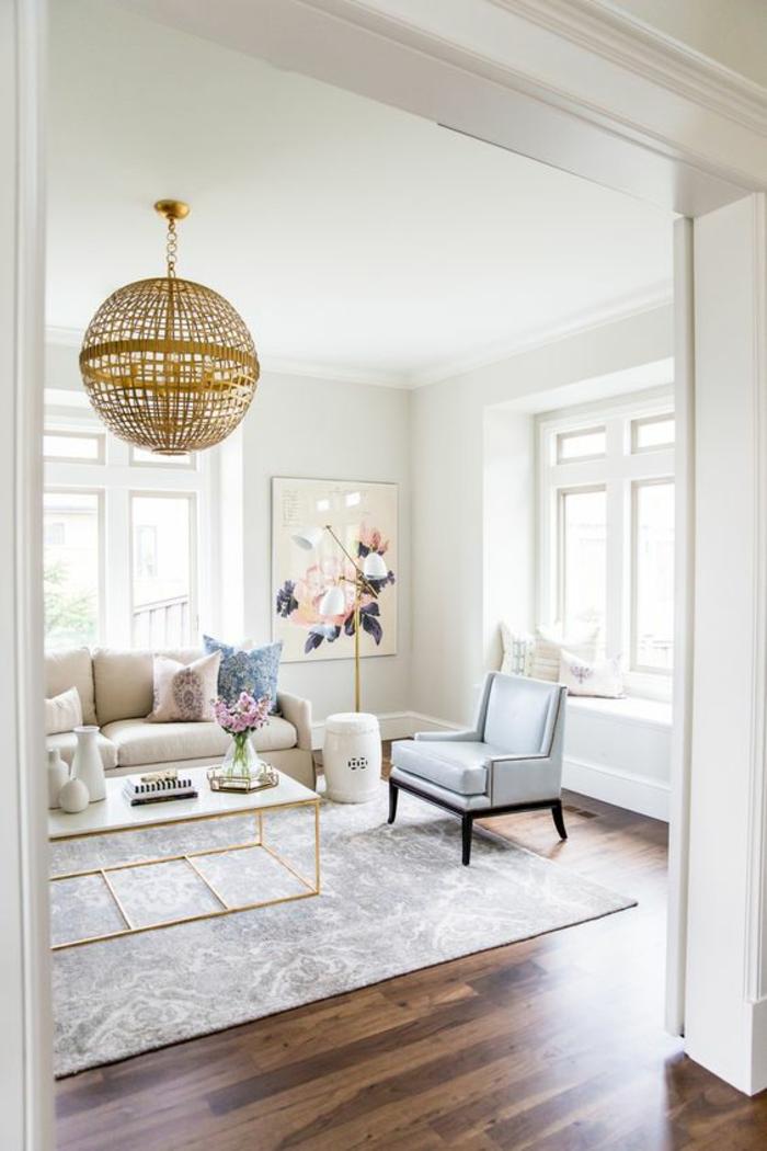 salon de luxe avec parquet en marron et beige, grande boule luminaire en métal doré, table avec plan blanc et pieds en métal doré