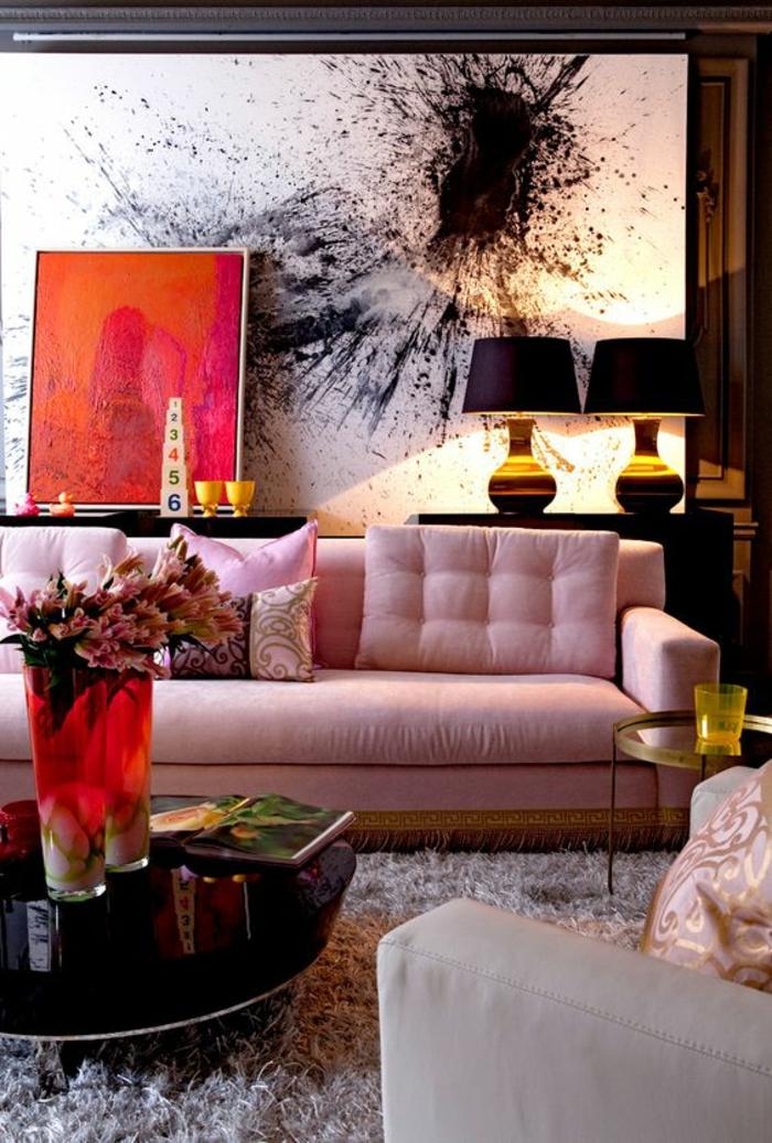 maison moderne de luxe, salon moderne de luxe avec table ronde basse, canapé en rose pastel avec deux grands coussins matelassés, tableaux en noir et blanc et en rouge et orange