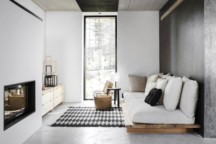 aménagement gain place d un petit salon noir et blanc élégant équipé d un canapé en palette au design épuré