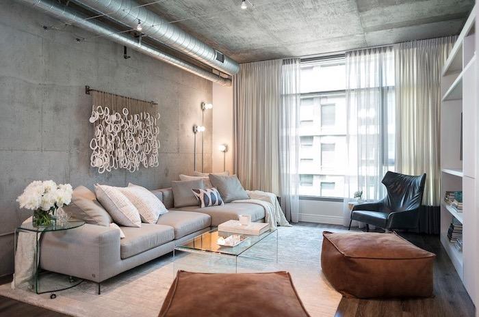 salon style industriel avec canapé gris, decoration murale intéressante, mur en béton, tapis blanc cassé et tabourets marron