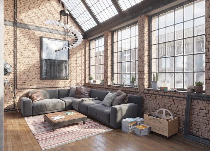 amenagement loft industriel avec canapé gris, table basse en bois minimaliste, caisse en bois rangement, parquet clair, murs en briques, lustre original