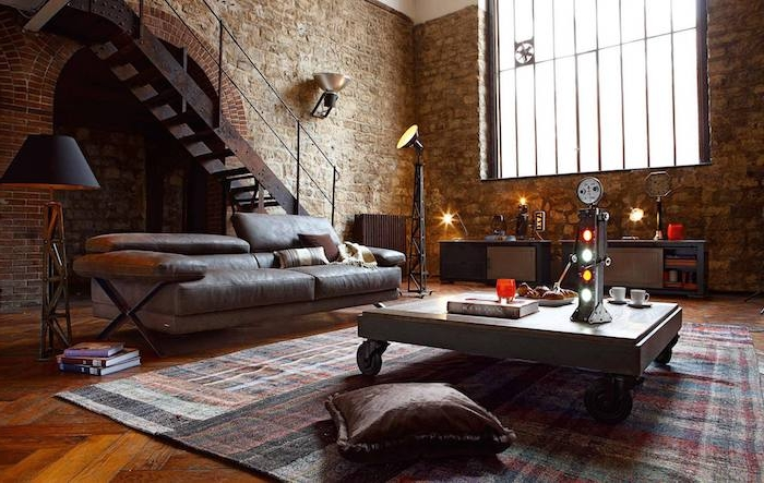 modele de table basse industrielle à roulettes dans un salon avec canapé en cuir gris, tapis à carrés, meuble en métal, coussin marron, mur en briques