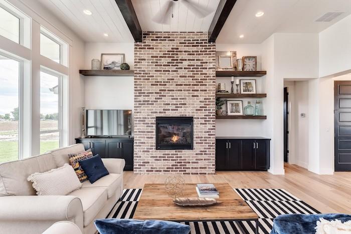 exemple de meubles style industrielle, table basse industrielle en bois et métal, canapé blanc cassé, cheminée en briques, poutres apaprentes