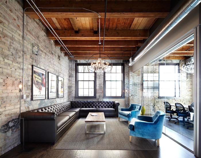 modele de table basse industrielle en acier et beton avec canapé d angle en cuir marron foncé et fauteuils bleus, suspensions originale, poutres apaprentes