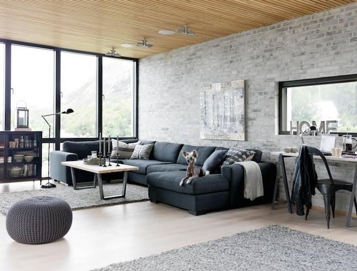 modele de table basse industrielle en bois et metal dans un salon loft avec canapé noir, tapis gris et pouf gris, plafond en bois, mur en briques grisées