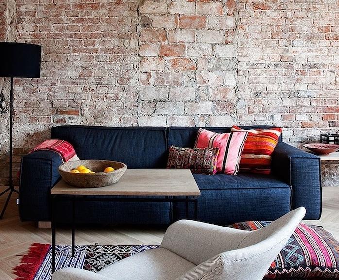 mur en briques dans un salon moderne avec canapé noir, parquet clair, table basse en bois et metal, tapis oriental
