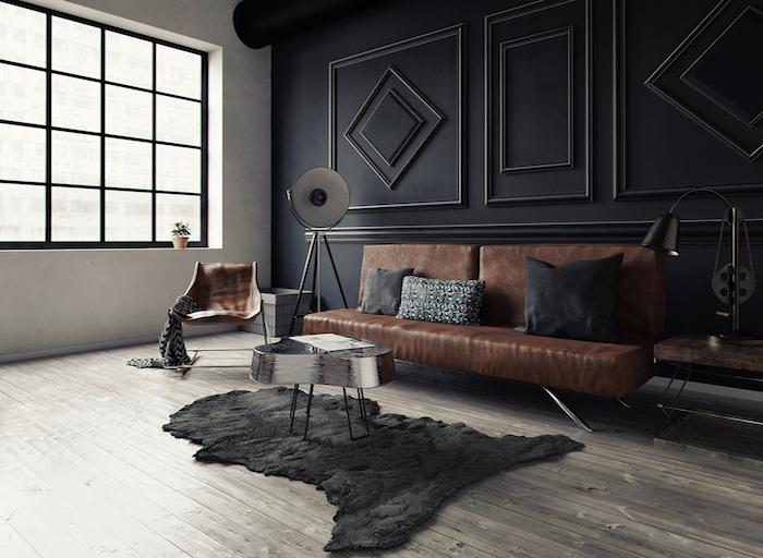meubles style industriel dans un salon loft avec mur noir à motifs geometriques, canapé en cuir, peau animale noire, table basse originale, fauteuil en cuir, parquet gris