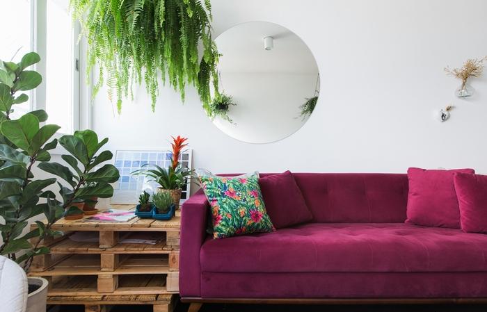 un salon aux accents verts plein de fraîcheur contraste table en palette et canapé en velours aux