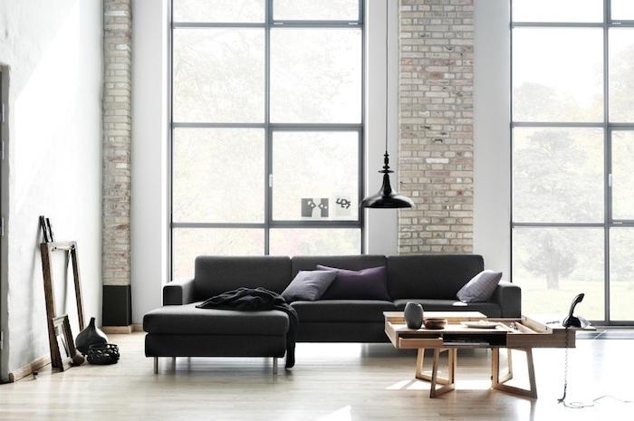 deco industrielle dans un salon spacieux avec pan de mur en briques, parquet clair, canapé noir, table basse en vois et deco de cadres vides