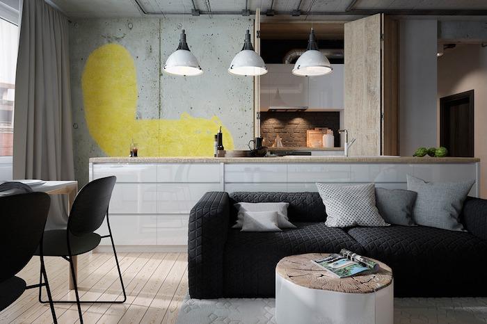 table basse industrielle en tronc de bois, canapé noir, coussins gris, parquet clair, suspensions industrielles, mur en fer avec tache jaune