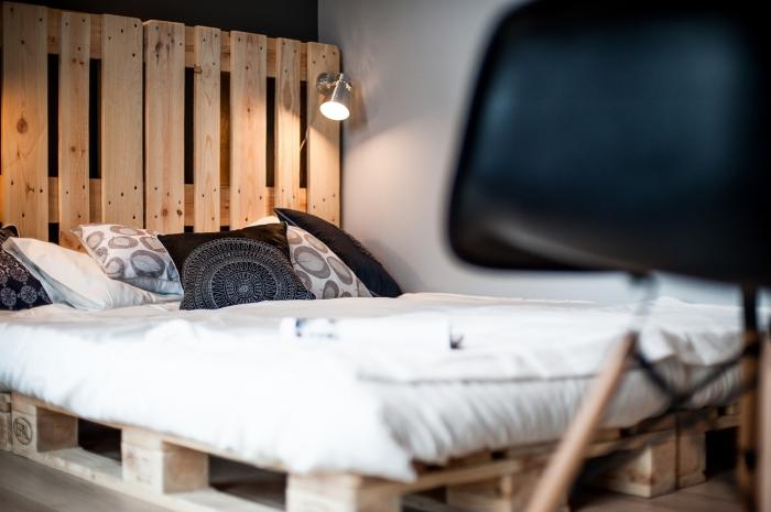 tete de lit en palette a faire soi meme, décoration de chambre à coucher avec lit en palette et coussins décoratifs en blanc et noir