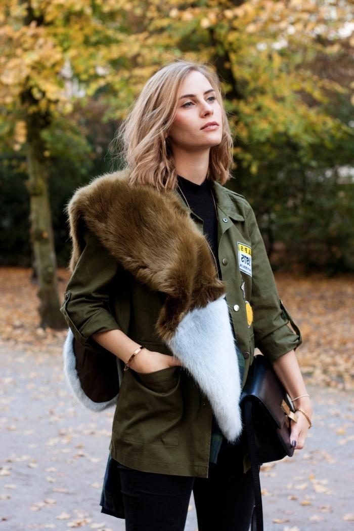 couleur kaki, manteau fourrure femme, coupe de cheveux mi-longs blond miel, pantalon et chemise noirs combinés avec écharpe faux fur et manteau kaki