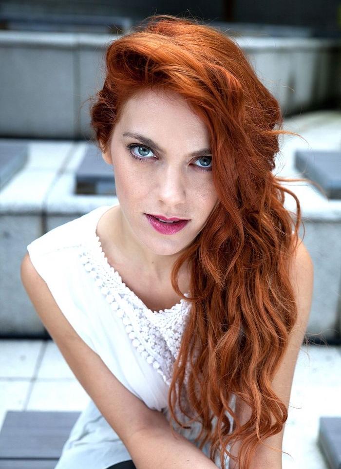 tie and dye roux sur de longs cheveux bouclés sur le coté, chemise sans manches blanche, des yeux bleus