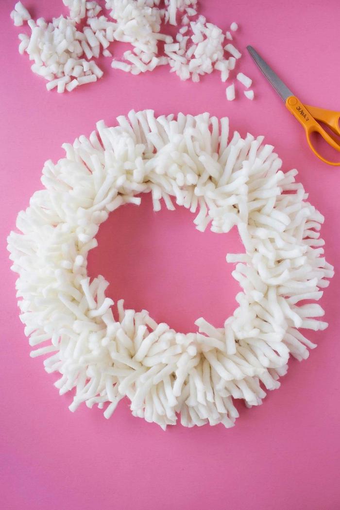 tuto bricolage de noel facile pour réaliser une couronne de l'avent douillette en fils de laine noués autour un cadre métallique