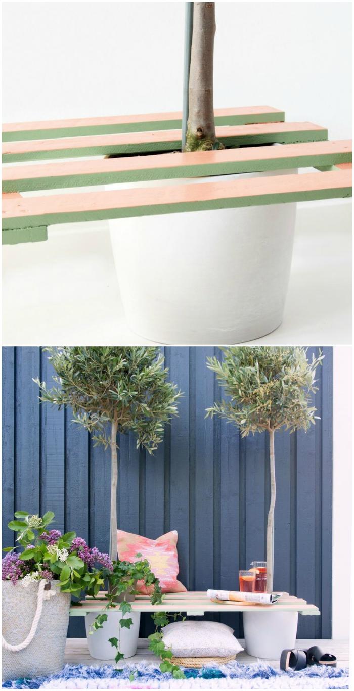 un banc palette original peint en couleurs pastel fixé entre deux arbres en pots