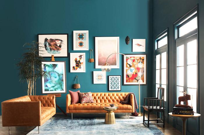 exemple de canapé pas cher, deux canapés en cuir sur un mur de fond en bleu canard, deco murale de cadres artistiques, table basse minimaliste