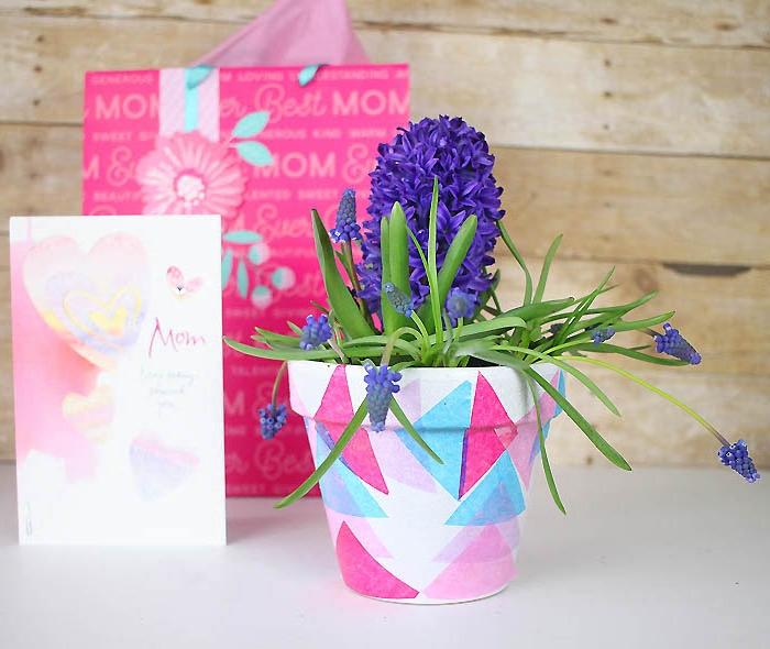 pot de fleur blanc customisé de triangles de papier colorées en bleu, rose et fuchsia, muguet, idée cadeau fête des mères a faire soi meme