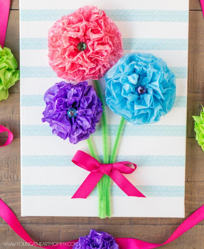 comment fabriquer des fleurs en papier de soie, rose, violet et bleu et tiges en cure pipe nouées d un ruban rose