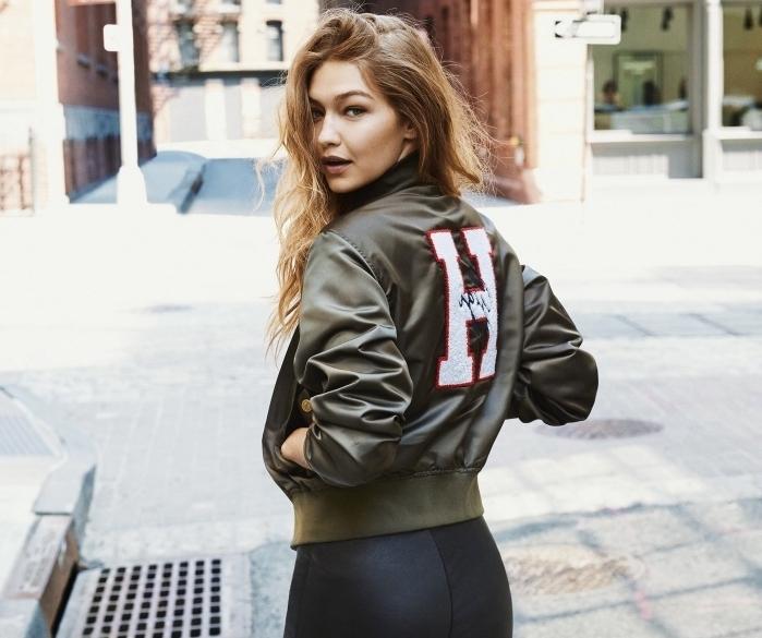 bomber femme, Gigi Hadid en pantalon slim noir et veste kaki, coiffure de cheveux naturelle avec coloration blonde cuivrée et boucles