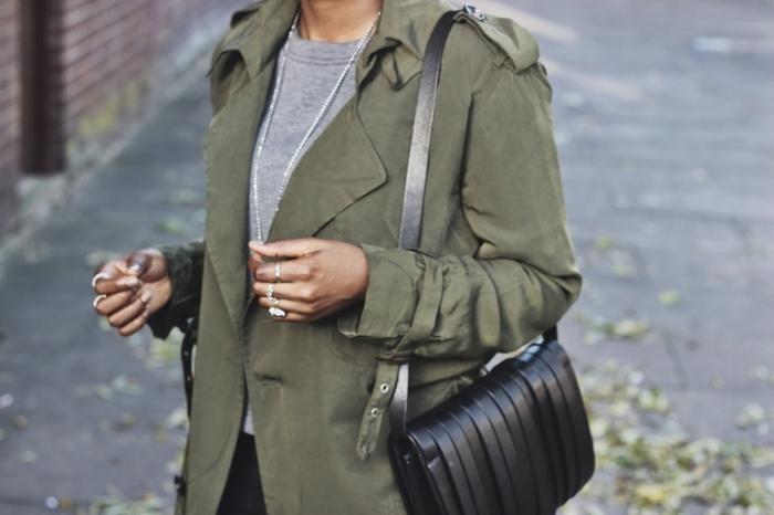 comment porter la veste kaki avec blouse grise et pantalon noir, sac à main en cuir noir avec franges décoratives