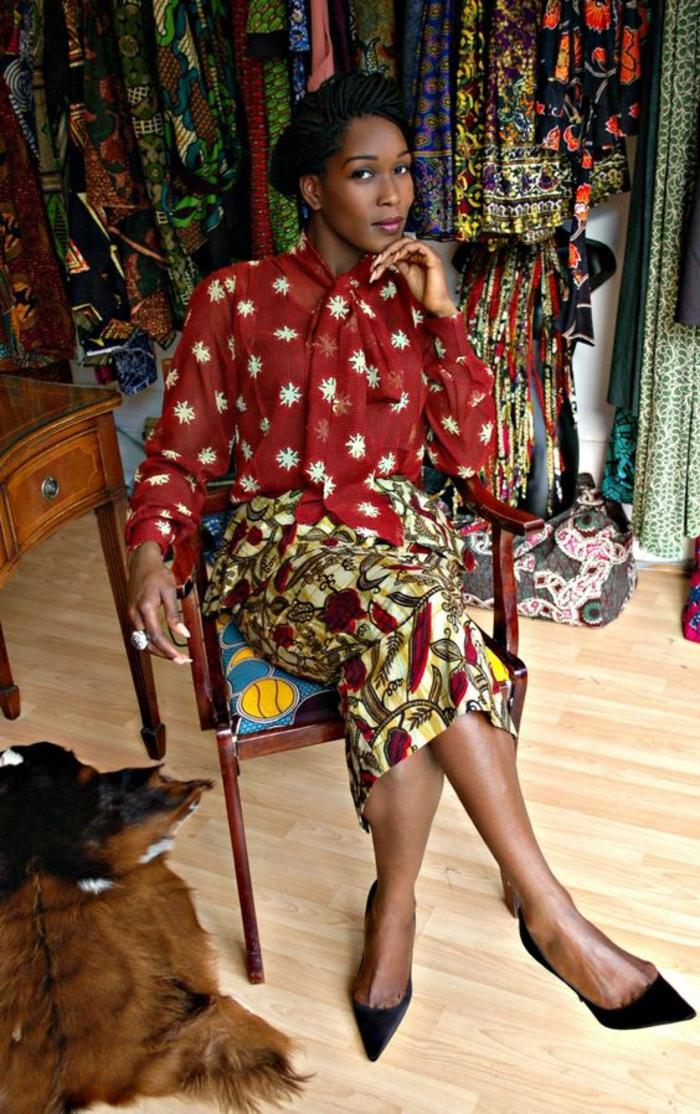blouse semi transparente en couleur brique, avec des manches longues et nœud devant, jupe longue africaine, motif africain plumes en rouge et fleurs et jaune
