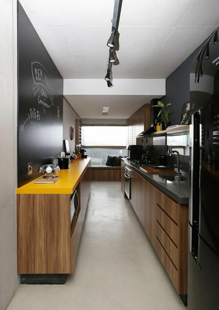 cuisine petit espace, cuisine en longueur, meubles n noir et jaune, carrelage blanc, tableau noir pour des notes sur un mur entier