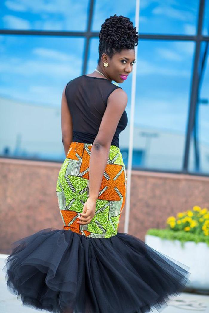 style habillé avec robe africaine en tulle noir et partie moulante en pagne africain, longueur de la jupe sous les genoux, robe avec la partie haute semi-transparente, sans manches