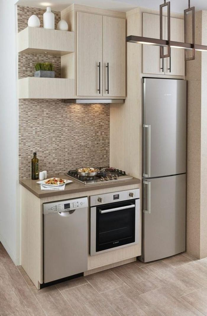 petite cuisine équipée, cuisine ouverte sur salon, parquet PVC en couleurs grisâtres, crédence en faïence beige et blanche, deux étagères massives en couleur beige crème, luminaire en métal couleur argent